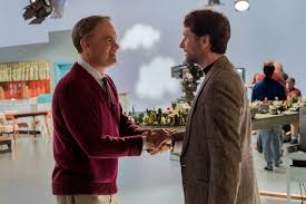 Tom Hanks, as Fred Rogers, shakes hands with journalist Lloyd Vogel, played by Matthew Rhys.